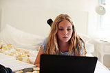 Teenage girl lying on bed working with laptop, close up