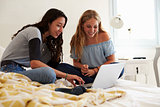 Two teenage girls on bed using laptop, surface level view