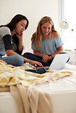 Two teenage girls sitting on bed using laptop, vertical