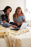 Two teenage girls sitting on bed using laptop, vertical