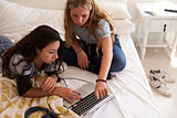 Two teenage girls on bed using laptop, elevated view close up