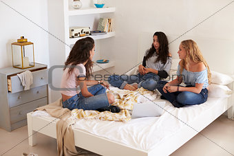 Three teenage girls sitting on bed with laptop talking