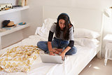 Teenage girl wearing headphones sitting on bed using laptop