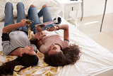 Teenage girls lying on bed using technology, elevated view