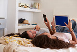 Teenage girls lying on bed talking and using technology