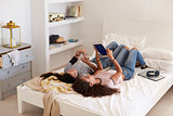 Two girls lying on bed using phone and tablet, elevated view