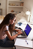 Teenage girl using laptop at a desk in her bedroom, vertical