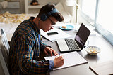 Teenage boy wearing headphones works at desk in his bedroom