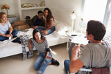 Teenage friends hanging out in bedroom, over shoulder view