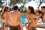 Teenage friends hanging out beside a swimming pool, back view