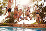 Teenagers jumping into an outdoor pool look to camera, Ibiza