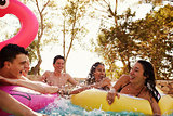 Teenage friends have fun with inflatables in a swimming pool