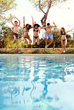 Happy teenagers jumping into an outdoor pool, vertical