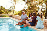 Two couples sitting at the edge of a swimming pool talking
