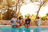 Two couples sit at poolside talking, front view