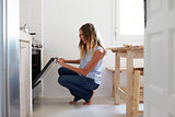 Woman squatting down in kitchen to look into the oven