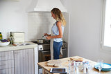 Woman standing at hob stirring food cooking in a saucepan