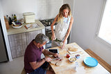 Couple prepare food and pour wine in kitchen, elevated view
