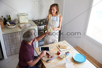 Couple drink wine and prepare food in kitchen, elevated view