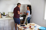 Couple preparing food together drink wine by the oven