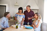 Two couples preparing food and drinking wine, front view