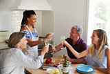 Two couples preparing dinner make a toast at kitchen table