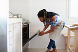 Woman bending down to look into the oven in her kitchen