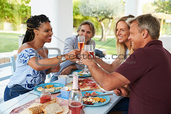Four friends making a toast at a dinner table on a patio