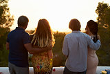 Two couples admire view from a rooftop at sunset, back view