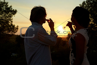 Adult couple drinking on a rooftop admiring the sunset