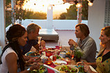 Two couples eating dinner on a roof terrace, close up