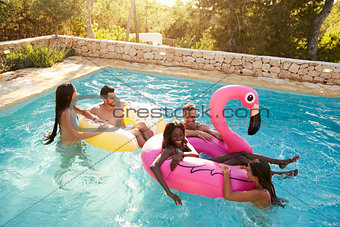 Group Of Friends On Vacation Relaxing In Outdoor Pool