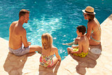 Rear View Of Family On Vacation Relaxing By Outdoor Pool