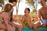 Family On Vacation Relaxing By Outdoor Pool