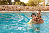 Father And Son On Vacation Having Fun In Outdoor Pool
