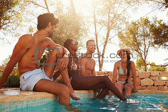 Group Of Friends On Vacation Relaxing Next To Outdoor Pool