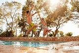 Rear View Of Children On Vacation Jumping Into Outdoor Pool