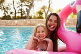 Mother And Daughter On Inflatables In Outdoor Swimming Pool