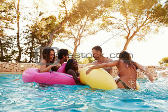 Group Of Friends On Inflatables In Outdoor Pool