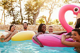 Portrait Of Friends On Inflatables In Outdoor Pool