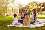 Family Relaxing On Blanket In Garden