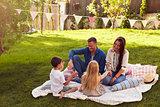 Family Relaxing On Blanket In Garden