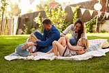 Parents Playing Game With Children On Blanket In Garden