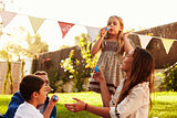 Parents Blowing Bubbles With Children In Garden