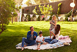 Parents Blowing Bubbles With Children On Blanket In Garden