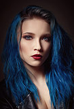 Closeup studio portrait of beautiful young woman with blue hair