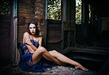 Beautiful young woman covered in cloth sits in abandoned train wagon