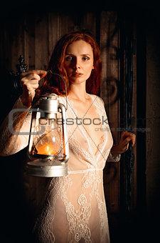 Portrait of sexy redhead girl with kerosene lamp