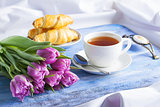 Breakfast with croissants tea purple tulips on blue wooden tray.