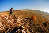 Wide angle view of a cyclist riding a bike on a nature trail in the mountains.